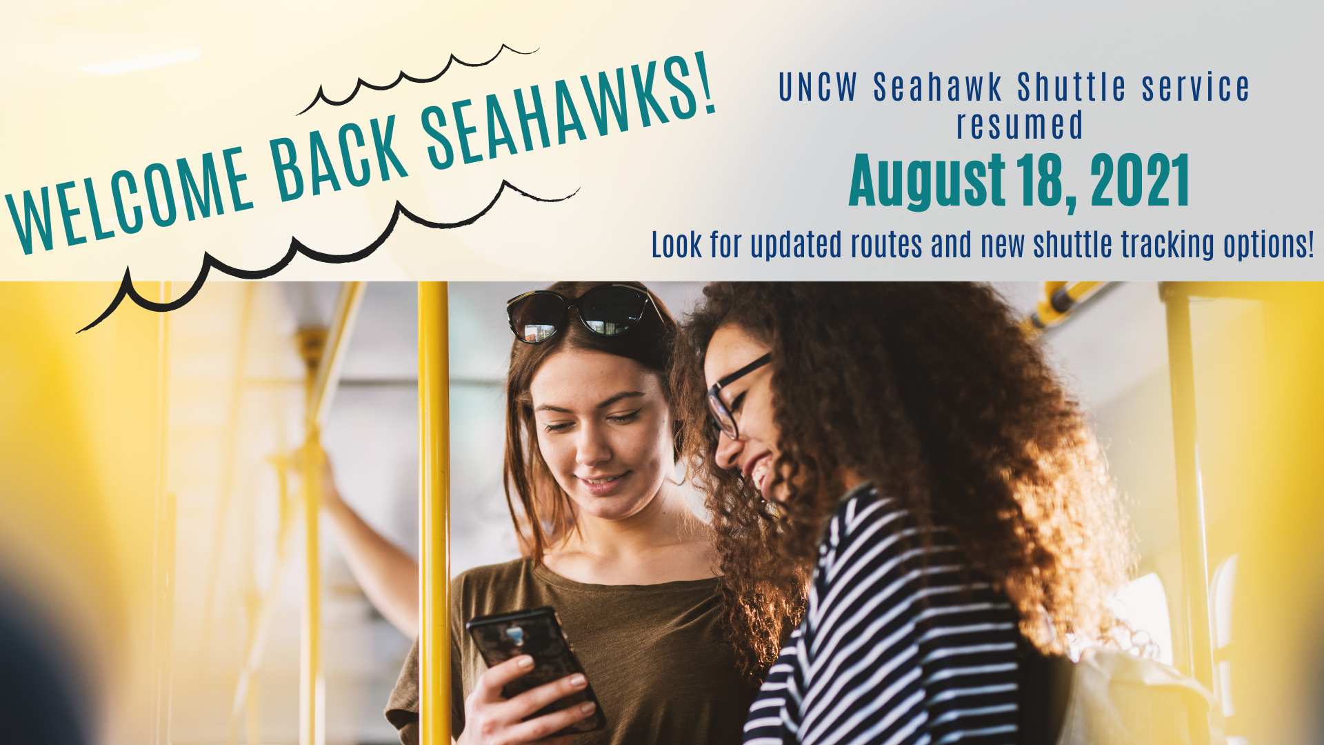 Welcome back Seahawks! UNCW Shuttle Service resumed August 18, 2021. Two women on a bus look at a phone together. They're both smiling.